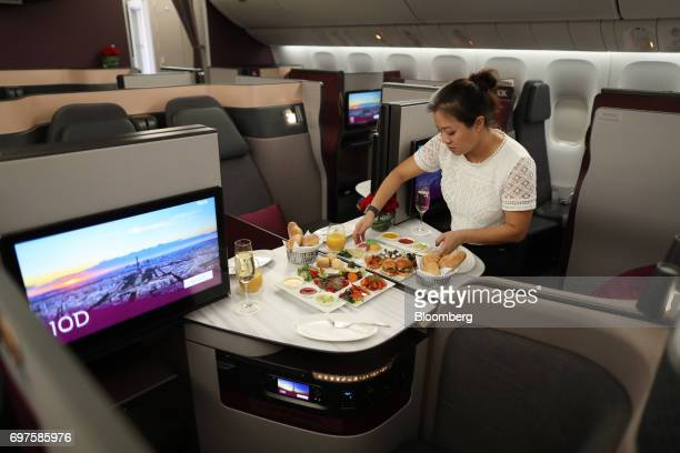 A cabin crew member arranges inflight food onboard a Qatar Airways Ltd Boeing Co 777 passenger aircraft during he 53rd International Paris Air Show...