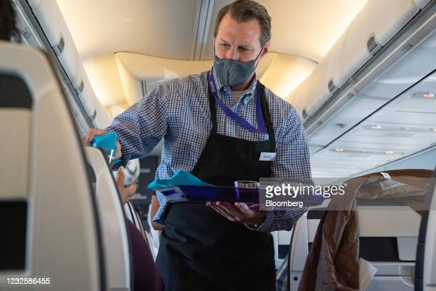 Cabin crew member distributes refreshments during in-flight service on the Avelo Airlines inaugural flight from Hollywood Burbank Airport in Burbank,...