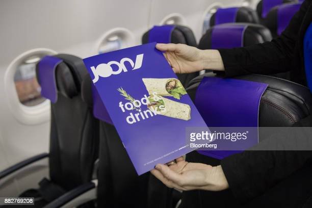 A cabin crew member holds a menu on board a Joon passenger jet the new lowcost carrier operated by Air FranceKLM Group at Charles de Gaulle Airport...