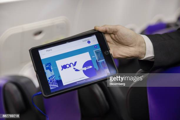 A cabin crew member holds a tablet device displaying free video streaming service on board a Joon passenger jet the new lowcost carrier operated by...
