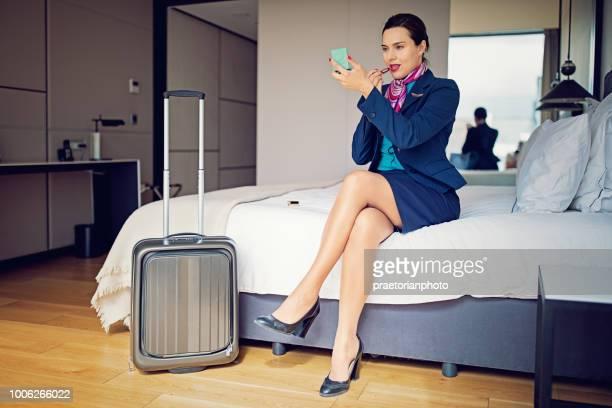 Cabin crew member is fixing her makeup before flight in the hotel room