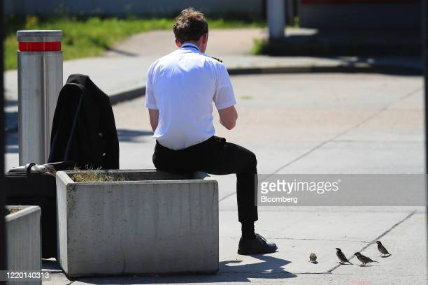 Cabin crew member rests outside Berlin Shoenfeld Airport after arriving from London, U.K., as European Union travel restrictions are lifted, in...