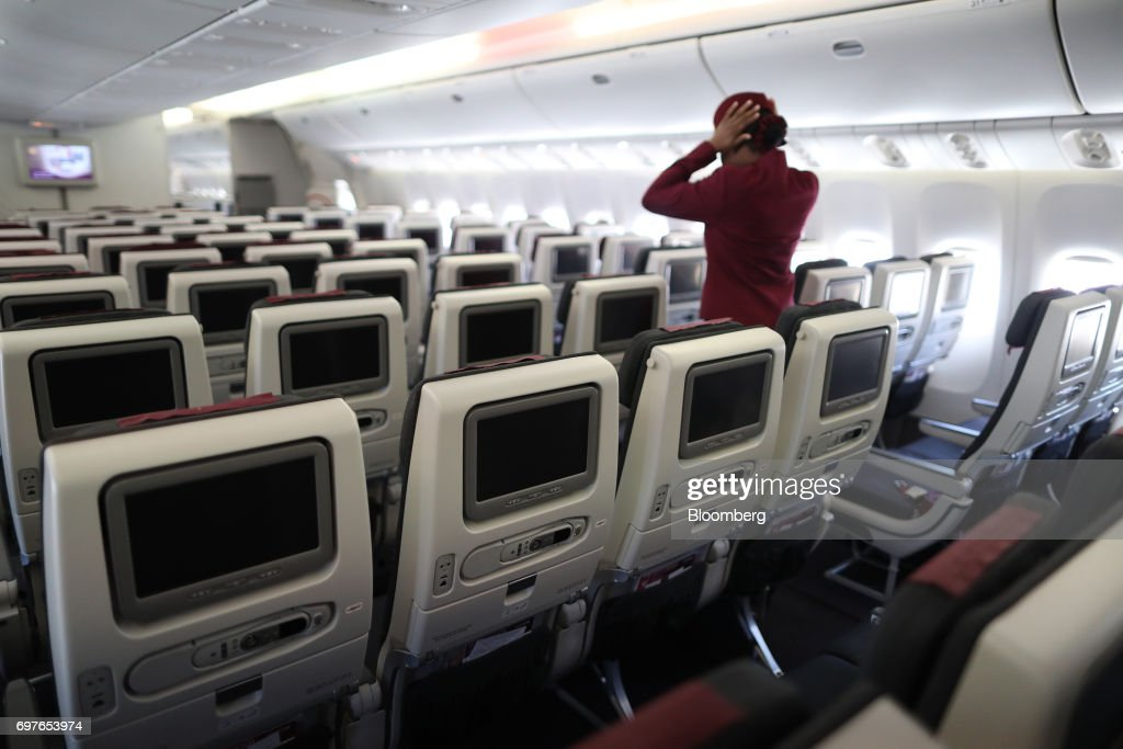 A cabin crew member walks down an aisle onboard a Qatar Airways Ltd Boeing Co. 777 passenger aircraft during the 53rd International Paris Air Show at Le Bourget, in Paris, France, on Monday, June 19, 2017. The show is the world's largest aviation and space industry exhibition and runs from June 19-25. Photographer: Chris Ratcliffe/Bloomberg via Getty Images