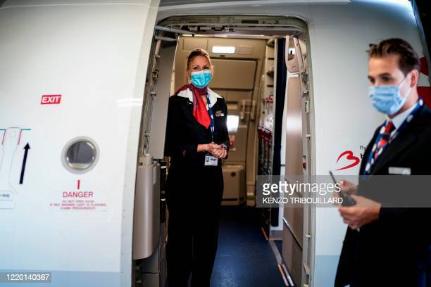 Cabin crew member wearing a protective face mask waits at the entrance of a Brussels Airlines plane, at Brussels Airport, in Zaventem, on June 15,...