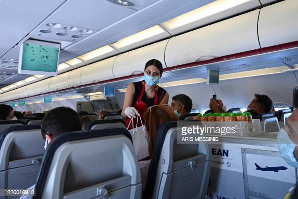 Cabin crew member wearing a protective facemask serves passengers aboard of a flight to the island of Santorini on June 13, 2020 as the country...