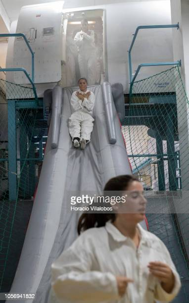 TAP cabin crew members jump from a smoke filled mockup A320 fuselage onto an evacuation slide during a practice of abandoning a plane on fire at TAP...