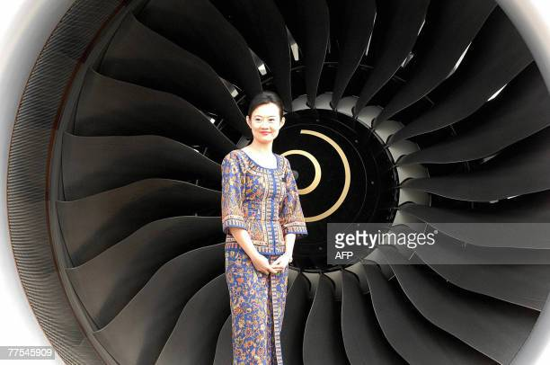 A cabin crew of Singapore Airlines poses next to one of the engines of the company's Airbus A380 passsenger plane parked at Sydney international...