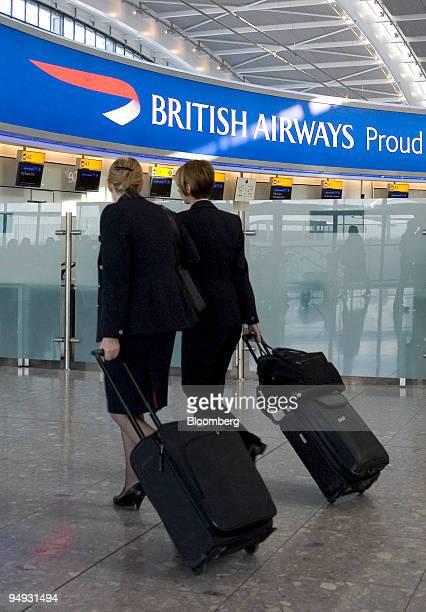 Cabin crew walk past a British Airways sign at Heathrow airport in London UK on Friday Oct 31 2008 British Airways Plc Europe's third largest carrier...