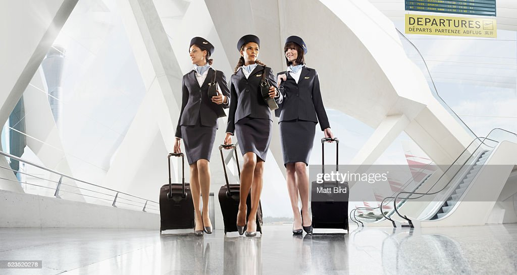 Cabin crew walking through large modern airport building for Korean air cabin crew requirements