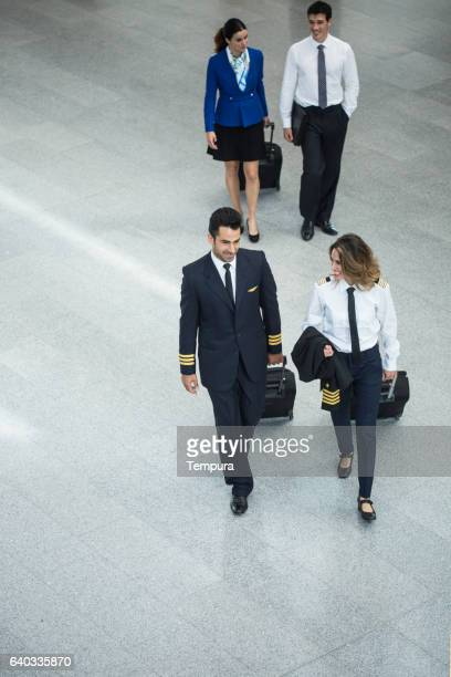 cabin crew walking through the airport. - besatzung stock-fotos und bilder