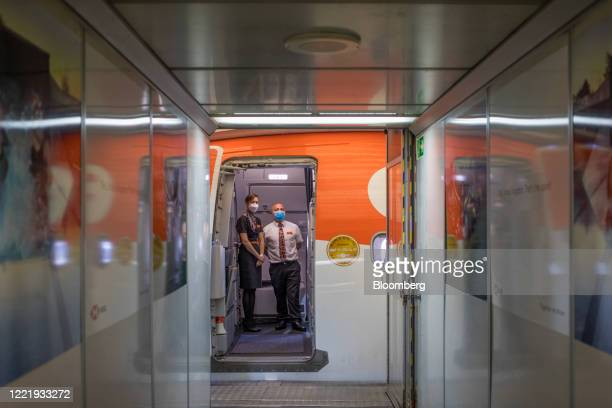 Cabin crew welcome passengers on board a flight, operated by EasyJet Plc, at London Gatwick Airport in Crawley, U.K., on Monday, June 22, 2020....