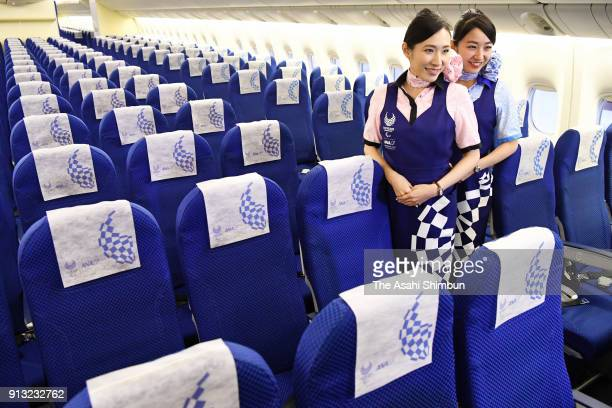 Cabin crews pose in the 'Hello 2020 Jet' of the All Nippon Airways during the press preview at a hangar of Haneda Airport on January 28 2018 in Tokyo...