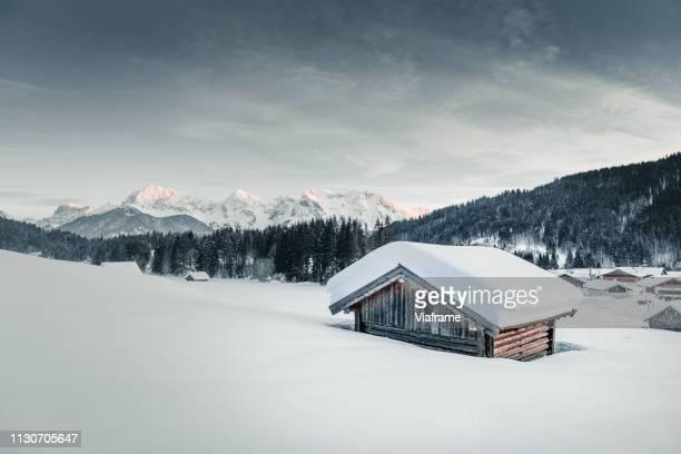 cabin in snowy mountains - schneebedeckt stock-fotos und bilder