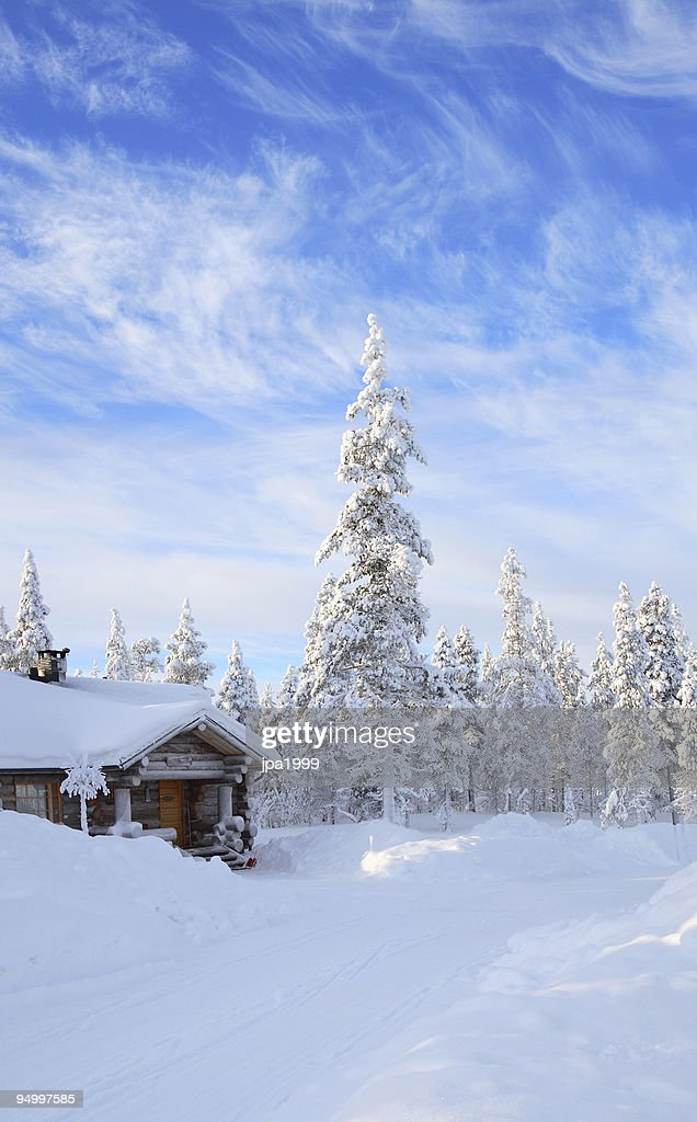 A cabin in the forest covered in snow  : Stock Photo