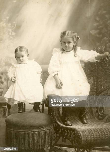 Cabinet card portrait of siblings a baby boy and confident young girl with ringlets in formal photography studio in front of painted backdrop taken...