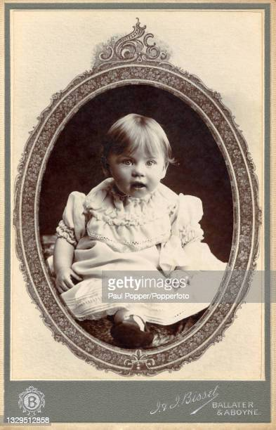 Cabinet card showing a baby wearing a long white dress with smocking around the neck and sleeves, white socks and black T-bar shoes, Aboyne,...
