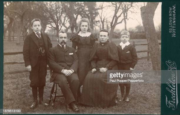 Cabinet card showing a family group comprising a man, woman and three children, the woman wears a dark, striped dress with high lace collar and gigot...