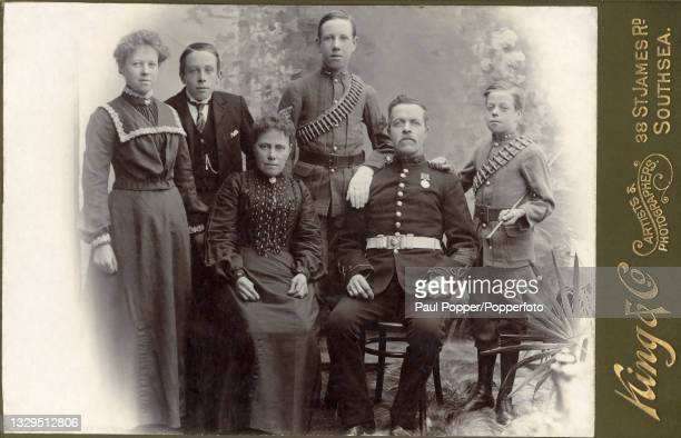 Cabinet card showing a family group, the women wear dresses with bishop sleeves and high necks, an older man wears the uniform of the royal artillery...