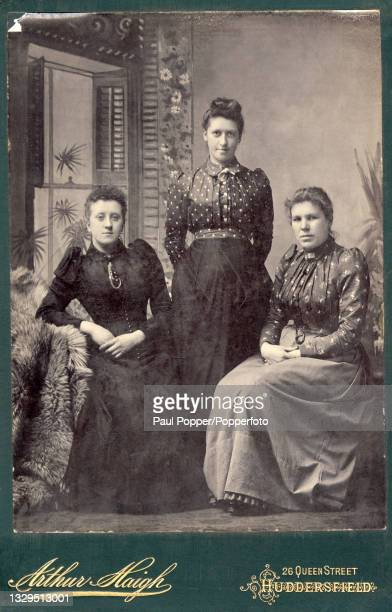 Cabinet card showing a group of three women, all three wear shirt waist dresses with puffed Italian sleeves and pleated bodices, one is in solid...