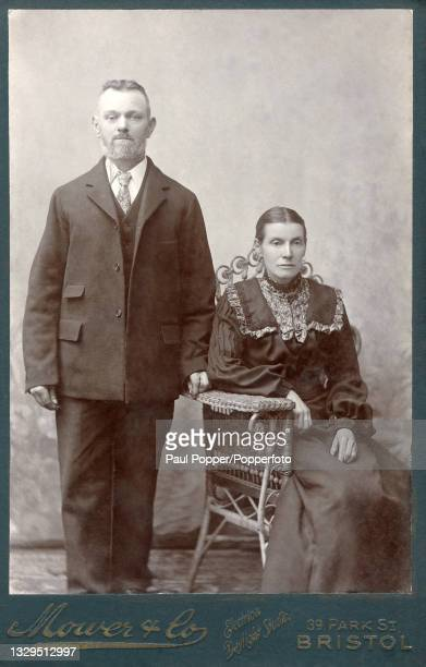 Cabinet card showing a man and woman in a studio setting, the woman is seated in a cane chair and wears a dark dress with pleated bishop sleeves, the...