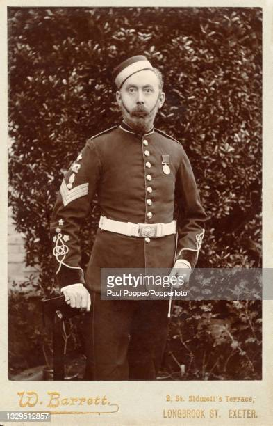 Cabinet card showing a man wearing a full Royal Artillery dress uniform with pillbox forage cap, Exeter, England, circa 1900.