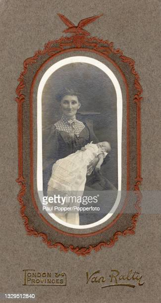 Cabinet card showing a woman holding a baby in her arms, the woman wears a dark dress with gigot sleeves and a high neck with a patterned yoke, the...