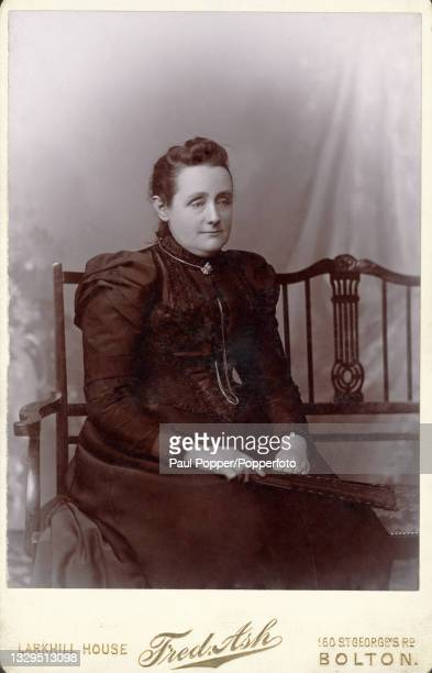 Cabinet card showing a woman wearing a dark dress featuring a tightly laced bodice, gigot sleeves and a high, frilled neck, she is seated and holds a...