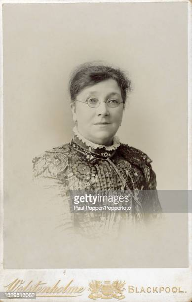 Cabinet card showing a woman wearing spectacles and a high necked dress, the dress features a ruff collar and a bodice with all over vertical pleats,...