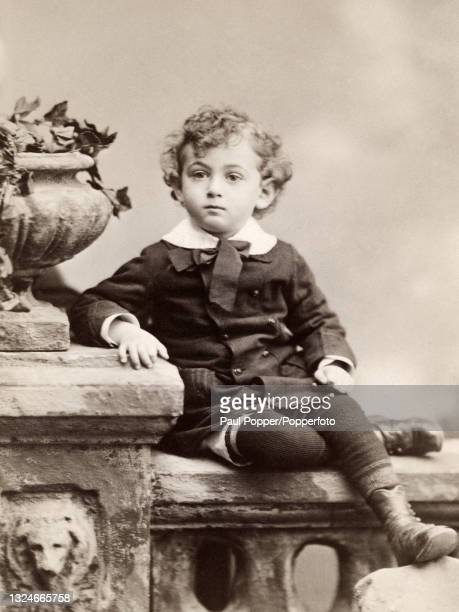 Cabinet card showing a young boy posed in a studio, he wears a double breasted wool tunic with white Peter Pan collar and neck tie, wool leggings and...