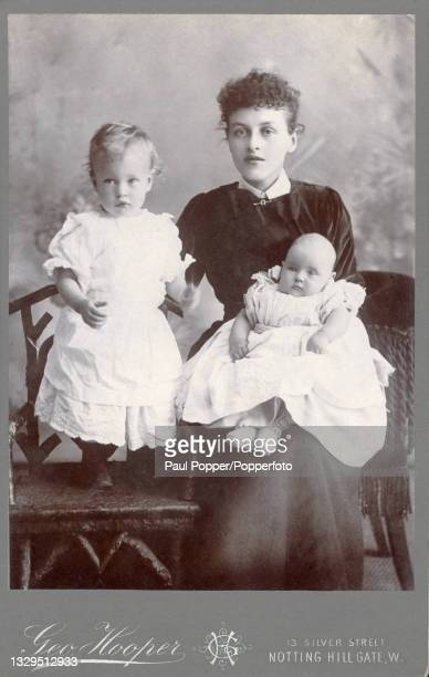 Cabinet card showing a young woman holding a toddler and a baby, both children wear white dresses with frilled sleeves and broderie anglaise trim and...