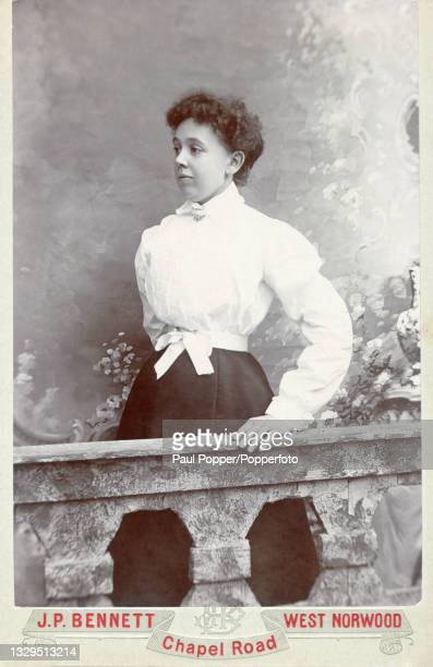 Cabinet card showing a young woman wearing a dark skirt, white satin tie belt and white blouse with bishop sleeves and full bodice, West Norwood,...