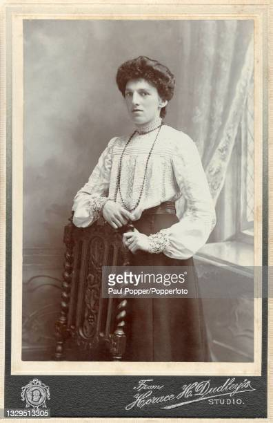 Cabinet card showing a young woman wearing a high necked white blouse, details include bishop sleeves with lace cuffs, all over delicate embroidery...