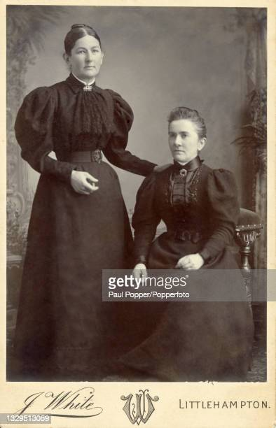 Cabinet card showing two women wearing dark gowns, both dresses feature ruffled lace neck ties, tight belts at the waist and wide gigot sleeves,...