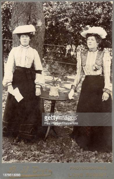 Cabinet card showing two women wearing full length dark skirts, light coloured blouses and white hats decorated with flowers, blouse details include...