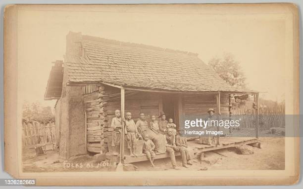 Cabinet card with an albumen print of three unidentified African-American women and seven children posed on the porch of a wooden house. The women...