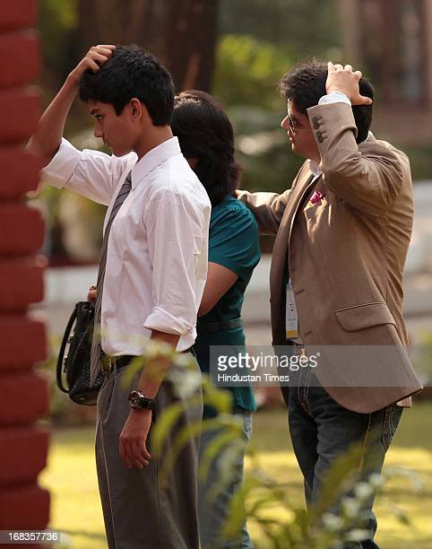 Cabinet Minister Jyotiraditya Scindia and his son Aryaman Scindia tries to make their hair for a photo at Doon Schools 75 years celebration at...