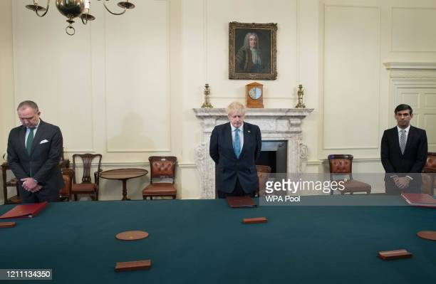 Cabinet Secretary Mark Sedwill, Prime minister Boris Johnson and Chancellor of the Exchequer Rishi Sunak stand inside the Cabinet Room of 10 Downing...