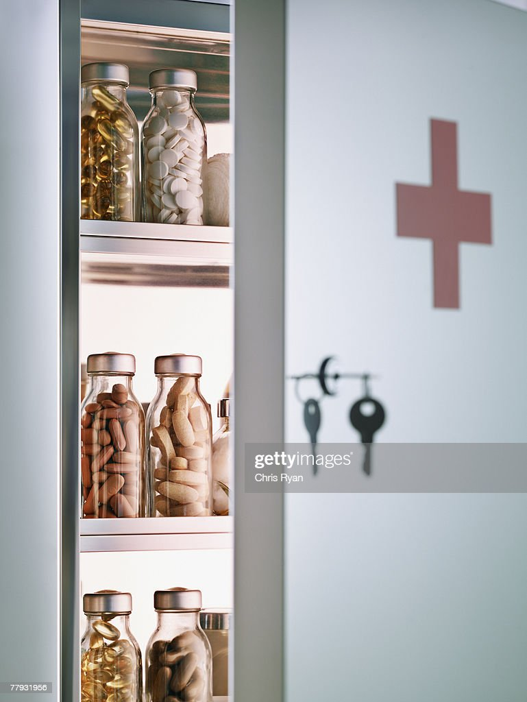 Cabinet with pill bottles next to hanging keys  : Stock Photo