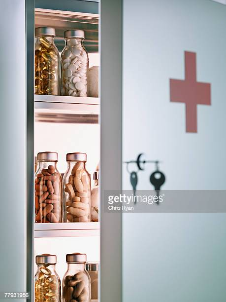 Cabinet with pill bottles next to hanging keys