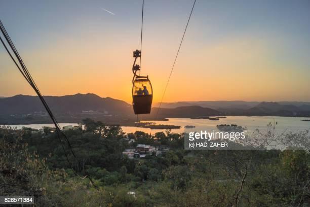 cable car at sunset over lake pichola | udaipur | rajasthan | india - hügelkette stock-fotos und bilder