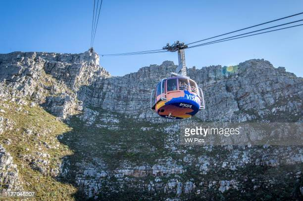 Cable car filled with passengers travels up to Table Mountain, located in Cape Town, South Africa.
