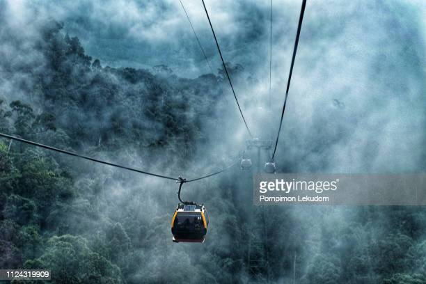 cable car go to top of hill in the mist - overhead cable car stock pictures, royalty-free photos & images