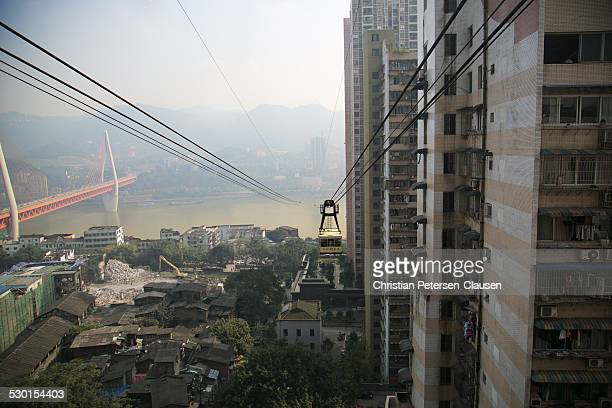 Cable car in Chongqing, Sichuan Province, China is crossing the Yangtze River with the Dongshuimen Bridge in the background.