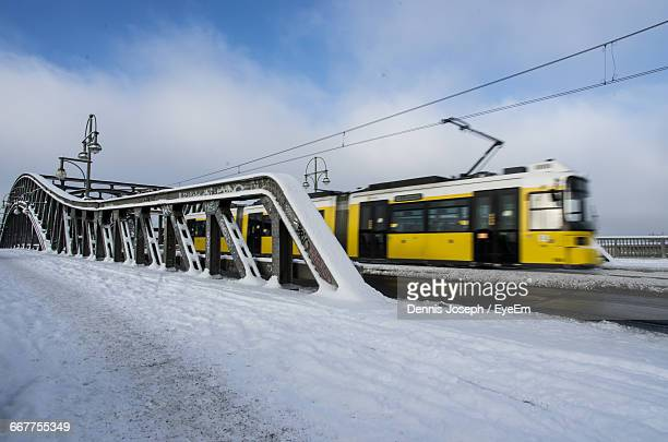 Cable Car Moving By Snow Covered Bornholmer Bridge Against Sky