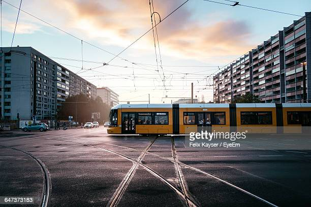 cable car on city street by buildings against sky - tram stockfoto's en -beelden