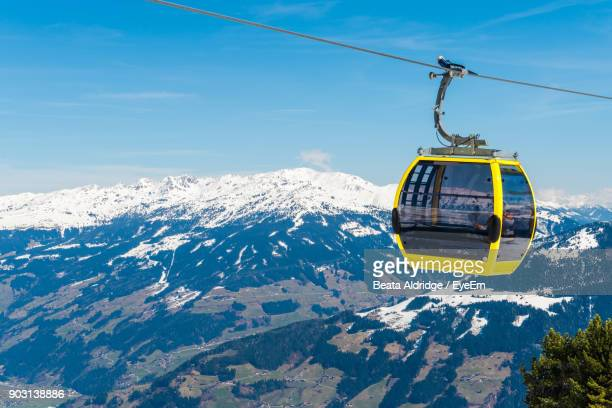 cable car over snow covered mountains against sky - overhead cable car stock pictures, royalty-free photos & images