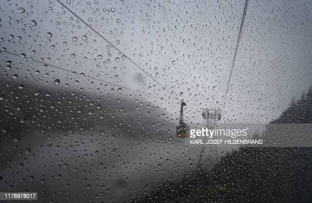 """Cable car riding in a foggy landscape is pictured through a rain-sprinkled window of another car on the aerial funicular """"Nebelhornbahn"""" on the..."""