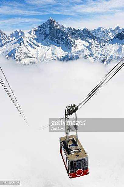 A cable car traveling up a snowy mountain