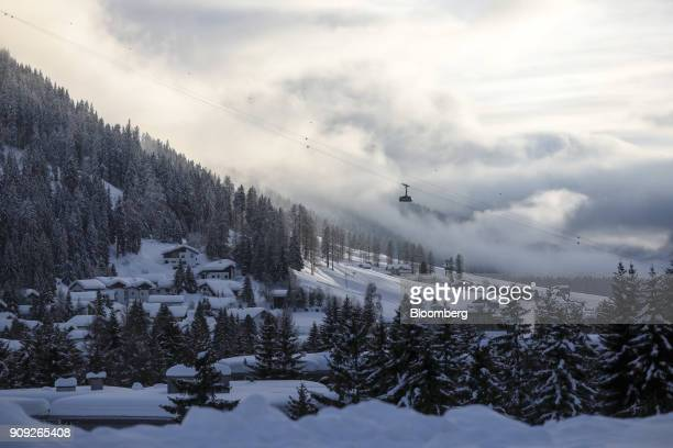 A cable car travels down a mountain as snow covers the landscape on the opening day of the World Economic Forum in Davos Switzerland on Tuesday Jan...