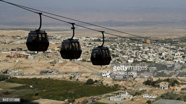 Cable cars bring tourists to the Mount of Temptation with the West Bank city of Jericho in the background on February 18 2017 / AFP / THOMAS COEX